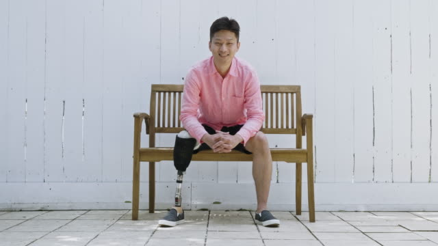 Real time video portrait of smiling Japanese disable man sitting on bench Real time video portrait of smiling Japanese disable man sitting on bench. disability stock videos & royalty-free footage