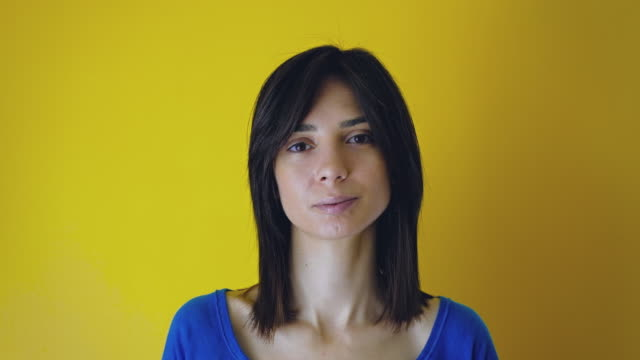 Real young woman looking at camera yellow background