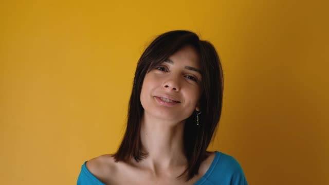 Real young woman looking happy against yellow background Real young woman looking happy against yellow background falling in love stock videos & royalty-free footage