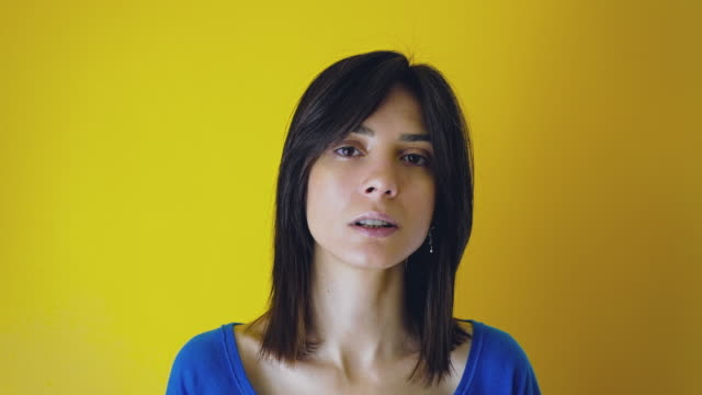 Real young woman making nervous gesture and looking at camera yellow background