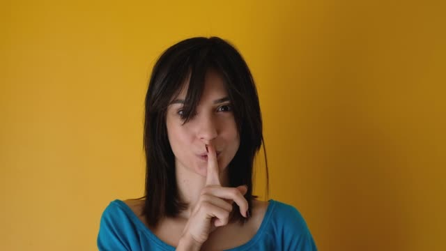 Real young woman making silence gesture and looking at camera yellow background