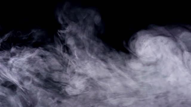 realistyczny dym, mgła, mgła izolowana na czarnym tle, tryb ekranu do mieszania efektu nakładki. strzał 4k w czasie rzeczywistym. - dym filmów i materiałów b-roll
