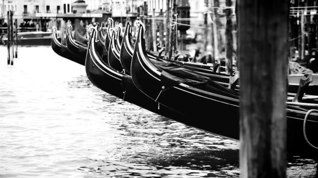 Real-time black and white footage of gondolas rocking on the waves of channel in Venice video