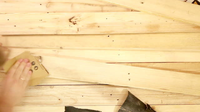 A real-time footage of a man polishing the wooden board with sandpaper video