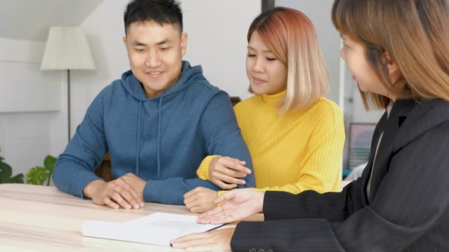 Realtor explain asian couple about contract and husband sign home contract at new home.buying new house real estate