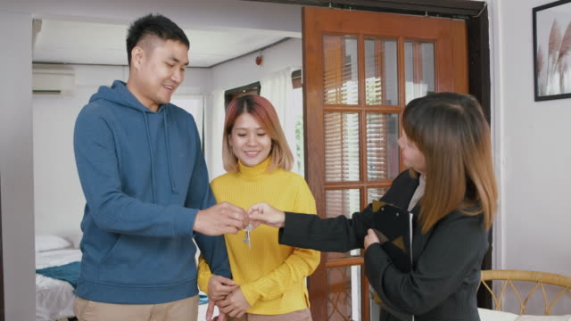 Realtor explain asian couple about house and give key to husband at new home and embracing each other.buying new house real estate.