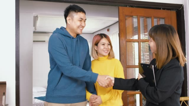 Realtor explain asian couple about house and give key to husband at new home and embracing each other.buying new house real estate