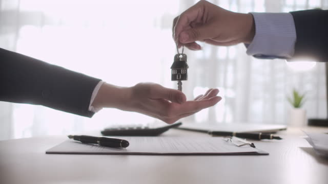 Realtor giving house keys to woman for House rental or House Sell at office, Slow motion