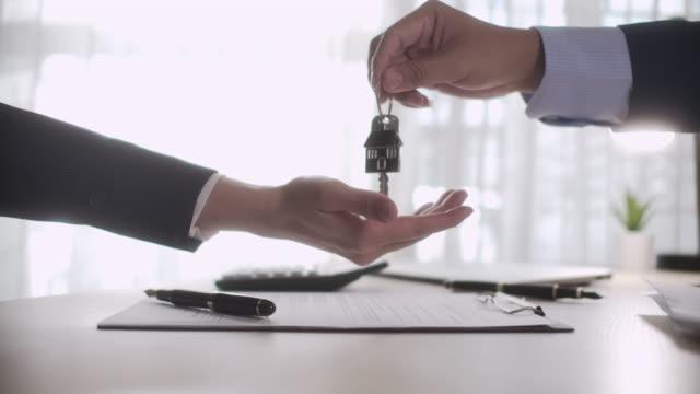 makler geben hausschlüssel an frau für hausvermietung oder haus verkaufen im büro, zeitlupe - hausschlüssel stock-videos und b-roll-filmmaterial