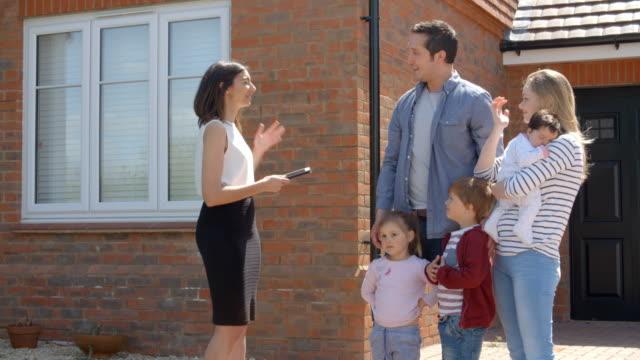 Makler außerhalb Haus mit für Verkauf Junge Familie – Video