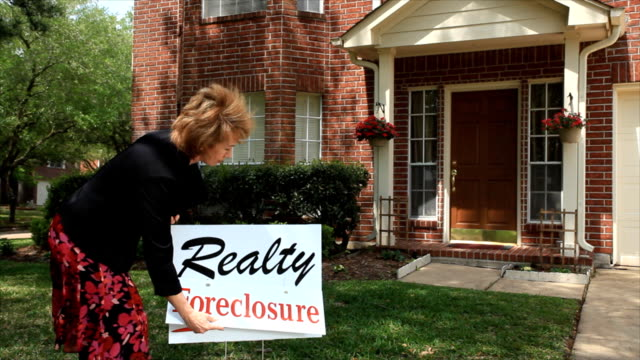 Realtor putting on foreclosure  sign video