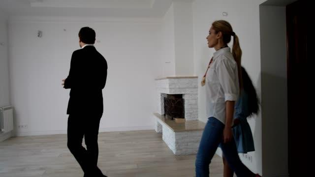 vídeos y material grabado en eventos de stock de realtor mostrando nueva casa a pareja de raza mixta - propiedad inmobiliaria
