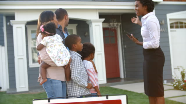 Realtor Stands Outdoors Showing Family Around House For Sale video