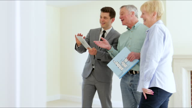 Realtor With Digital Tablet Shows Senior Couple Downsizing Around Retirement Home