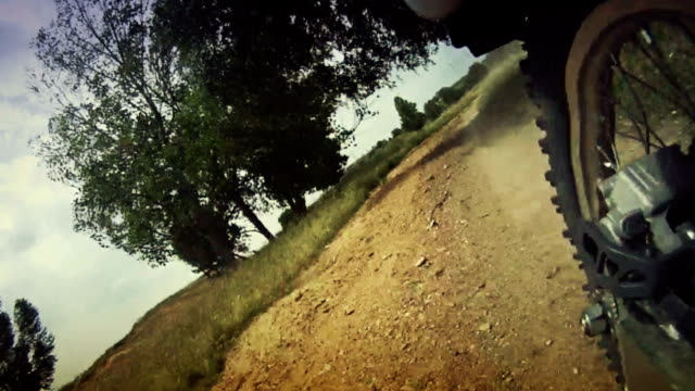 posteriore su scheda telecamera da motociclista di motocross equitazione in polvere - bike tire tracks video stock e b–roll