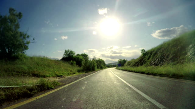 Rear pov view of fast sport car driving on rural road against sun shining on blue sky video