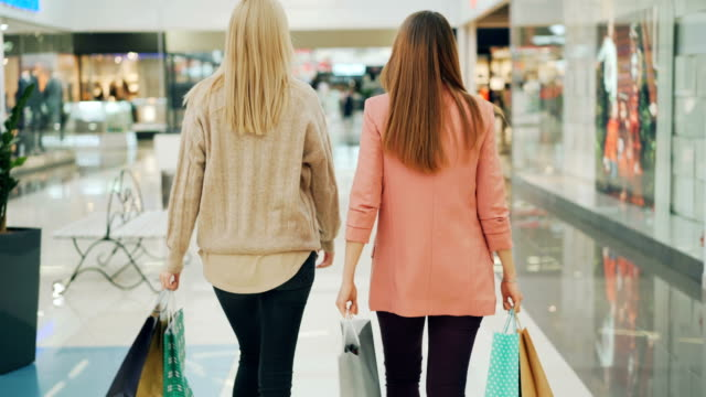 rear shot of slender young women walking in shopping mall holding paper bags and looking around at goods. happy customers, shiny shop windows are visible. - borsa della spesa video stock e b–roll