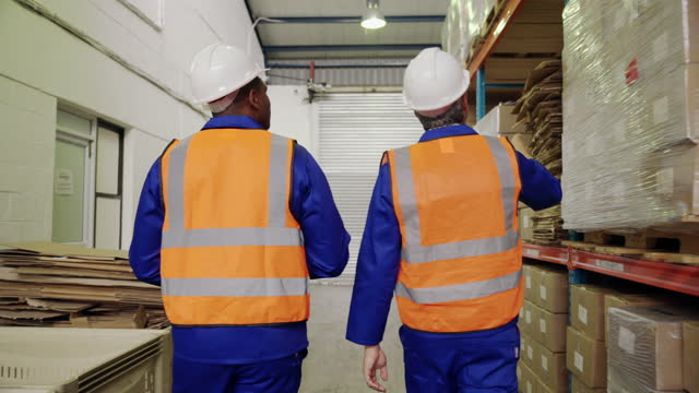 Rear shot of two male warehouse worker in safety vest and hardhat examine the stock in the large warehouse