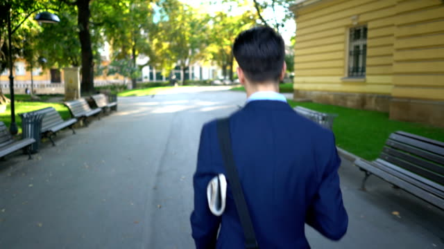 Rear shot view of one young businessman walking on the street and holding newspaper under his arm. video