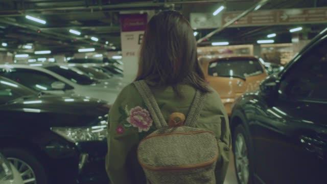 vídeos de stock e filmes b-roll de rear view : asian woman walking at the underground car park - fugir