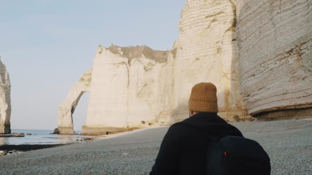 Rear view Caucasian tourist man with backpack walking along sea shore to white arch cliff at sunny Etretat slow motion.