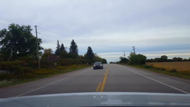 対向車線で遅い車両を追い越すリアビュー。 車の視点pov危険な運転操縦は、車両を渡すために次の車線に黄色のライン上の操縦。 - 後方点の映像素材/bロール
