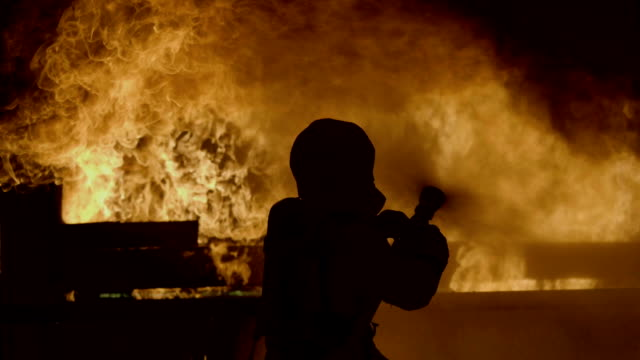 vídeos de stock e filmes b-roll de rear view : firefighter work - labareda
