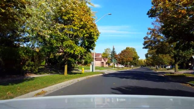日中の住宅街の道路ベンドを運転する車の後部からの背面図。 郊外の通りの明るい昼間の空に沿って回転する車両の後ろの車の視点pov。 - 後方点の映像素材/bロール