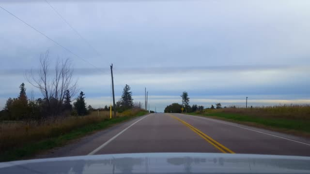 rear view from back of car driving rural countryside road under overcast day.  car point of view pov behind vehicle country street under cloudy sky. - сельская дорога стоковые видео и кадры b-roll