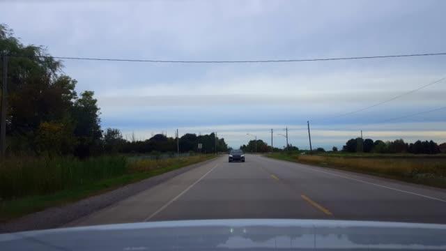 曇りの日の下で後部交通と田舎の道を運転する車の後ろからの後部眺め。 曇り空の下の車両カントリーストリートの後ろに車の視点pov。 - 後方点の映像素材/bロール