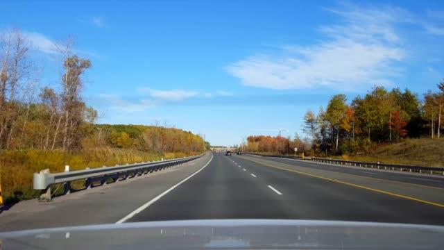 日中の田舎道を運転する車の後ろからのリアビュー。 車の視点は、車両国の州間高速道路や高速道路やターンパイクや高速道路や高速道路の後ろにpov。 - 後方点の映像素材/bロール