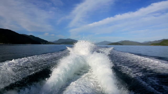 Rear View From Boat Speeding on a Lake DSLR point of view video from the rear view of a boat in the summer.  The splashing water from the engine is in the foreground and the lake, mountains and the mostly blue sky in the background. behind stock videos & royalty-free footage