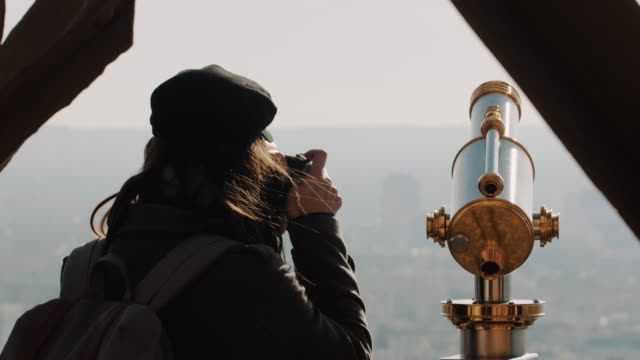 Rear view happy elegant photographer woman taking a picture of Paris view on top of famous Eiffel Tower slow motion.