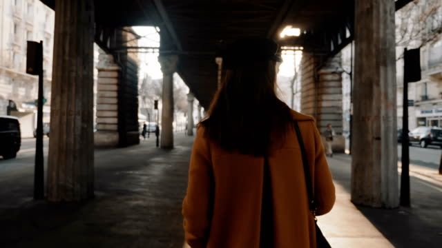 rear view happy stylish fashion blogger woman exploring paris streets under sunny high line metro flyover slow motion. - city walking background video stock e b–roll