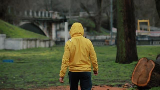 rear view man go away in a park - colore saturo video stock e b–roll