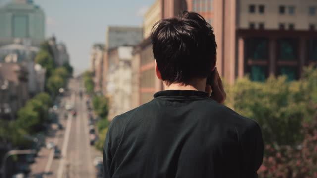şehirde smartphone tarafından konuşan arka görüş adam - i̇nsan sırtı stok videoları ve detay görüntü çekimi