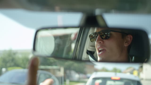 close up: rear view mirror reflection of angry man yelling during a traffic jam. - ingorgo stradale video stock e b–roll