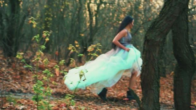 rear view mysterious woman in luxurious puffy aqua color dress runs away looks back. fabulous princess in gothic autumn forest. silk fabric dark long hair flutter in motion. fog, orange fallen leaves - сбежавший из дома стоковые видео и кадры b-roll