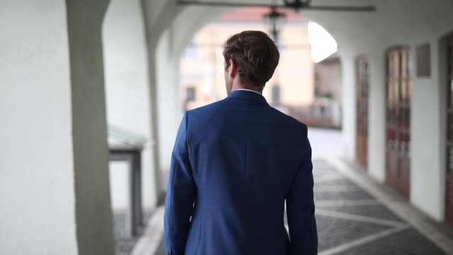 rear view of a businessman wearing navy suit walking with attitude