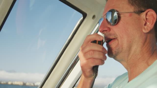 무전기를 사용하여 보트에 백인 남자의 뒷모습 - 중년 남자 스톡 비디오 및 b-롤 화면