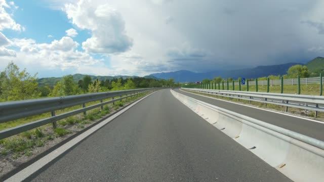 rear view of a driving car on a highway - сельская дорога стоковые видео и кадры b-roll