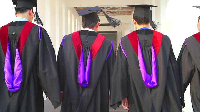 Rear view of a group of graduate students walking on a ceremony.(Slow motion) video
