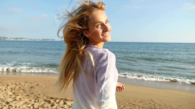 Vista posterior de una mujer feliz corriendo en la playa - vídeo