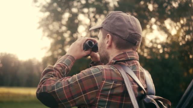 草原で双眼鏡で見ているハンターの背面図(スローモーション) - バードウォッチング点の映像素材/bロール