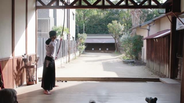 彼の道場で練習している日本の射手の背面図 - 武道点の映像素材/bロール