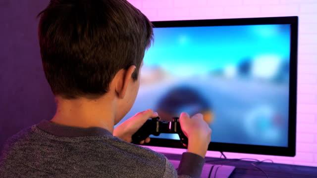 stockvideo's en b-roll-footage met achteraanzicht van een jongetje spelen racespel - sportwedstrijd