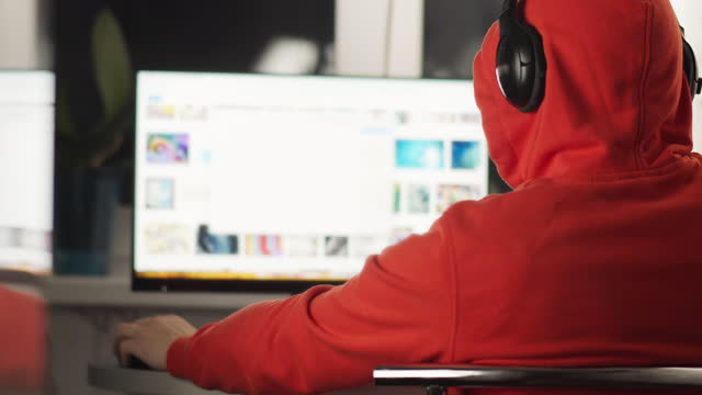 Rear view of a man in a hood and headphones working behind a monitor screen