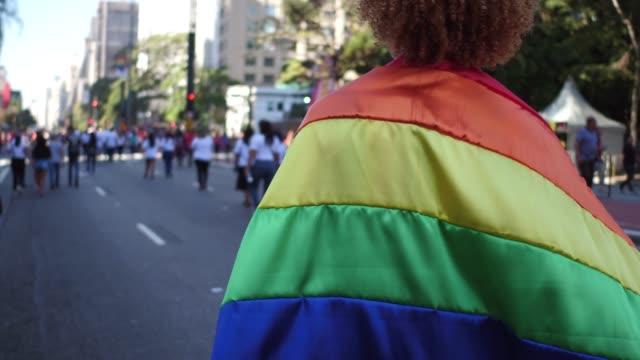vista posteriore di un uomo che cammina con una bandiera arcobaleno durante la parata lgbt - sfilata video stock e b–roll