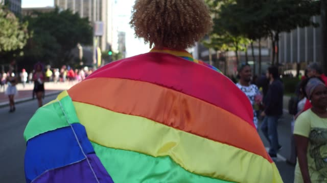 Rear view of a man walking with a rainbow flag during LGBT parade Rear view of a man walking with a rainbow flag during LGBT parade pride stock videos & royalty-free footage