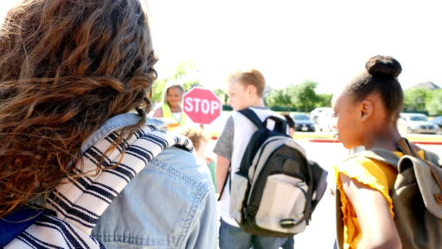 vídeos y material grabado en eventos de stock de vista trasera de una chica preadolescente esperando cruzar el cruce de peatones frente a la escuela - escuela media